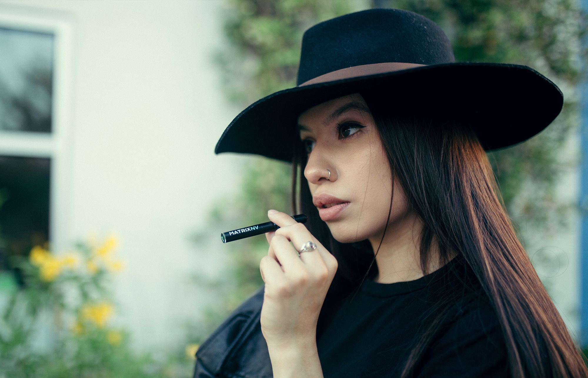 woman wearing a hat holding a vaping pen